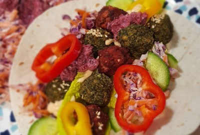 red and green falafel on a wrap with salad