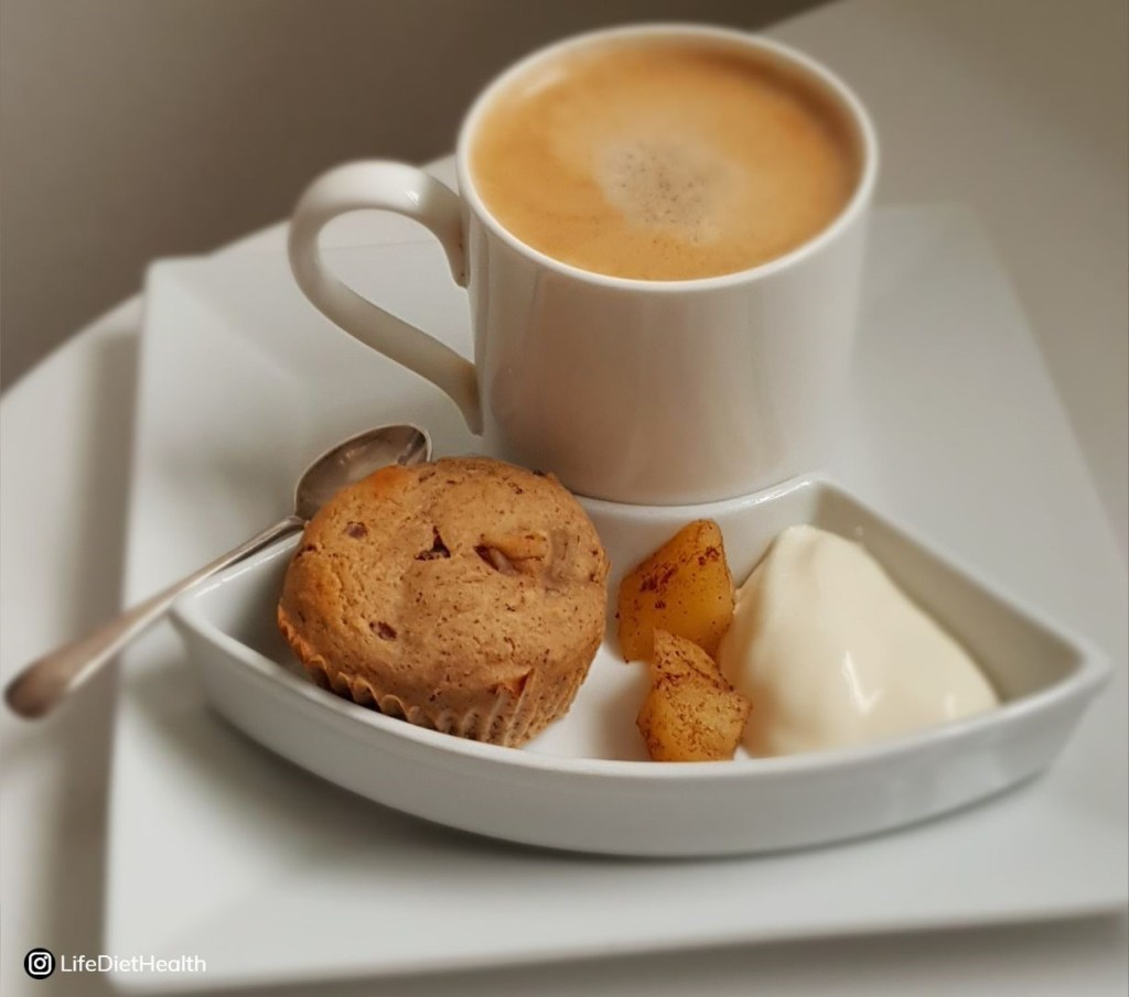 Coffee in white china with muffin, apple compote and yogurt