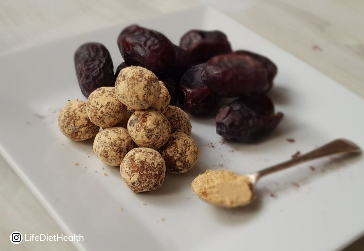 peanut butter balls ina pyramid shape with dates and a spoon of pb powder