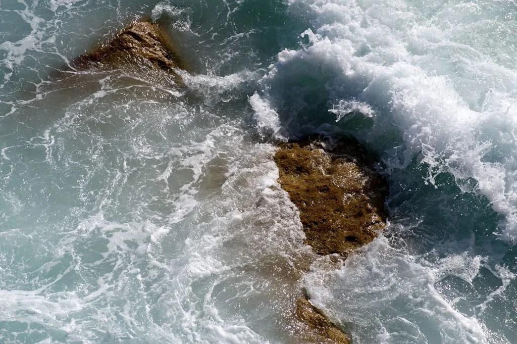 Photograph of ocean wave washing over rocks at Bondi Beach