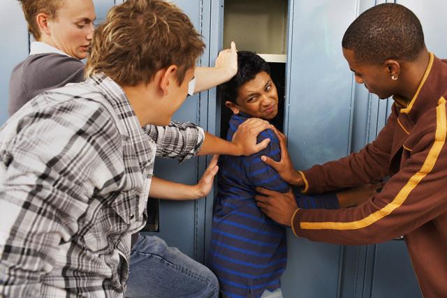 Group of Teens Stuffing Boy in Locker --- Image by © Radius Images/Corbis