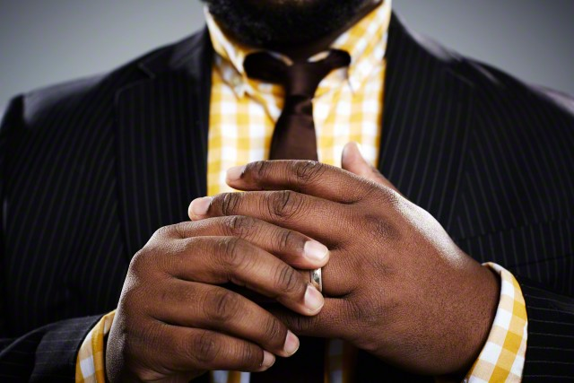 Close up studio portrait of mid adult businessman touching his wedding ring