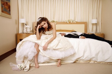 Bride disappointed with groom passed out on hotel bed --- Image by © Unlisted Images/Corbis
