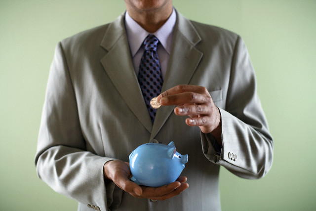 Businessman with Piggy Bank --- Image by © Tim Pannell/Corbis