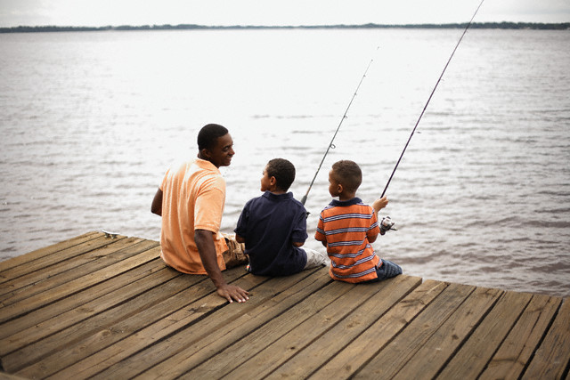 Father and Sons Sitting on Lakeside Pier --- Image by © David P. Hall