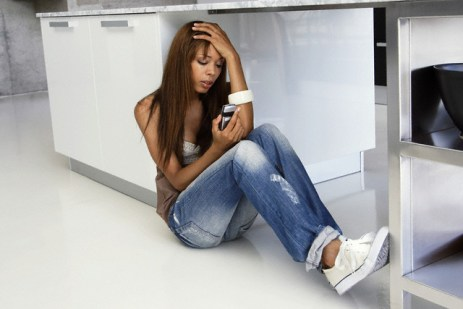Woman sitting on floor with a cell phone --- Image by © Tomas Rodriguez/Corbis