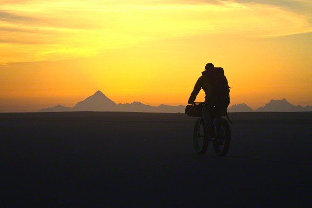 Man fatbiking on a remote beach near Yakutat, Alaska.