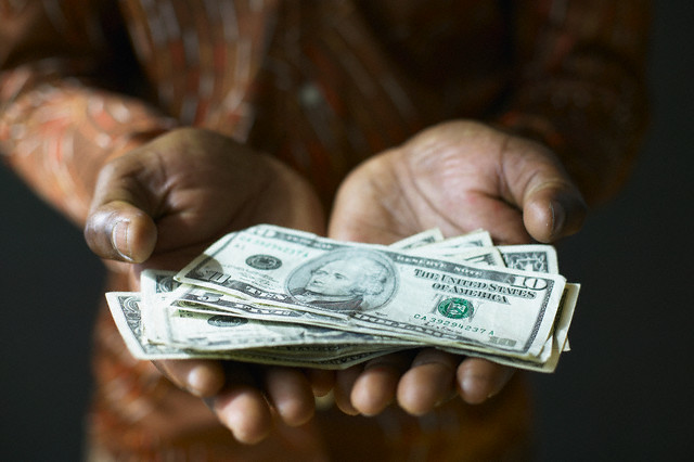 Hands Holding Money --- Image by © Stephen Welstead/LWA/Corbis