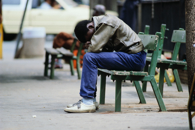 Unemployed man sitting on a bench, with his head in his hands --- Image by © Gideon Mendel/Corbis