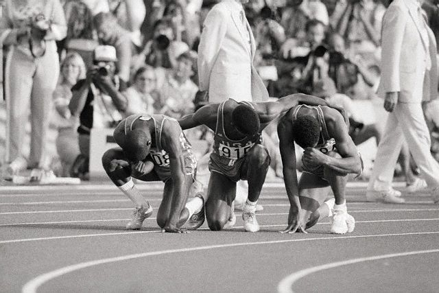 After a three-medal, 200-meter race at the 1984 Olympics, Thomas Jefferson (left-right), Carl Lewis, and Kirk Baptiste pause on the track for a prayer of thanks. --- Image by © Bettmann/CORBIS