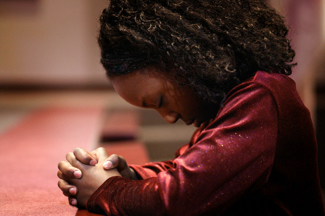Girl Bowing Head in Prayer --- Image by © Don Hammond/Design Pics/Corbis