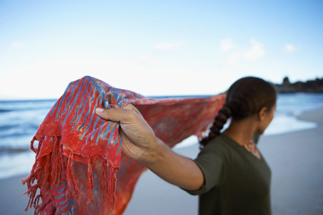 Woman standing on beach, holding shawl behind back, side view, close-up, focus on foreground --- Image by © Juice Images/Corbis
