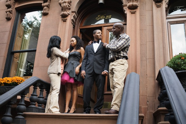 Couple going to prom with parents on front stoop
