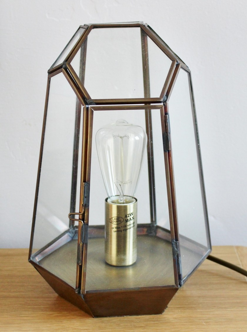 Litecraft Terrarium Candle Lantern Table Lamp - Antique Brass, featuring edison screw filament squirrel cage light bulb. Lamp turned off in daylight.