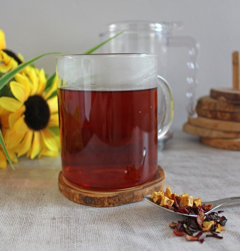 Photo of Adagio Tea in a glass mug, with diffuser behind, tea on spoon to the front.