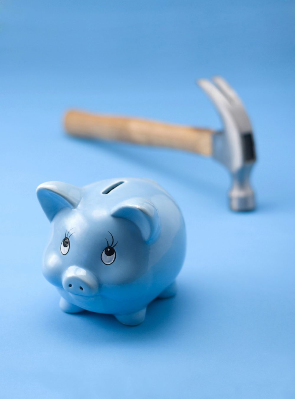 Blue piggy bank with hammer in the background