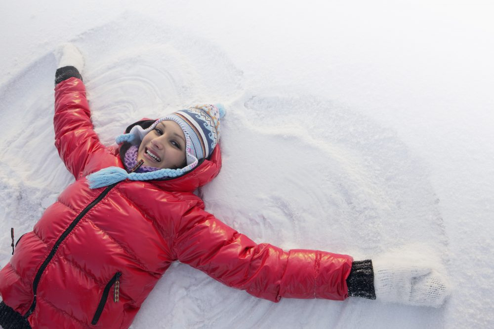 Lady laying in the snow making a snow angel