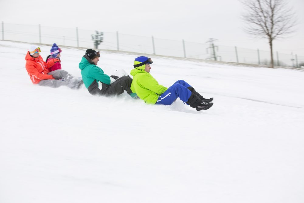 Side view of young friends sledging on snow covered slope