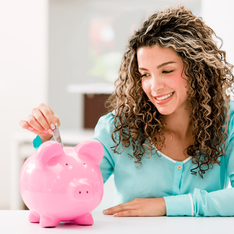 Lady putting a coin into a piggy bank