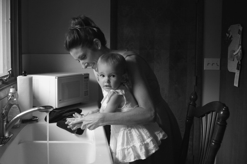 mother with child standing on chair doing dishes