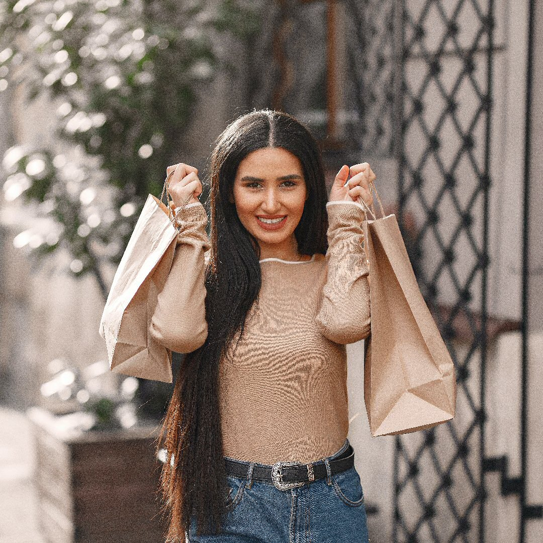 cheerful-woman-smiling-while-walking-with-shopping-bags-3867527