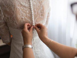 woman buttoning wedding dress