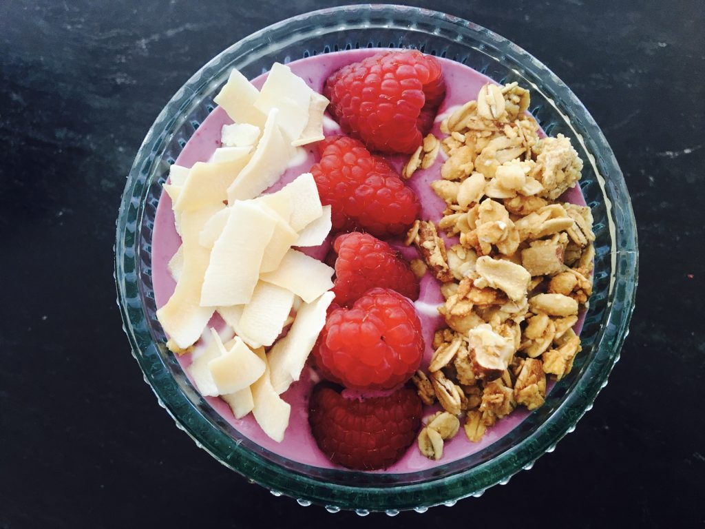 Smoothie Bowl with Coconut Chips, Granola and Raspberries