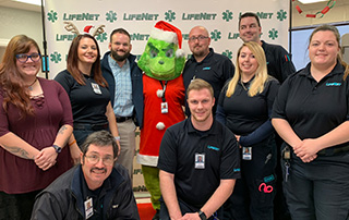 LifeNet EMS paramedics and EMTs pose with the Grinch during Photos with the Grinch at LifeNet EMS in Stillwater, Oklahoma.