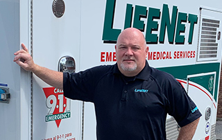 Klay Hall, LifeNet Director of Operations in Hot Springs, Arkansas, stands beside a LifeNet Ambulance.