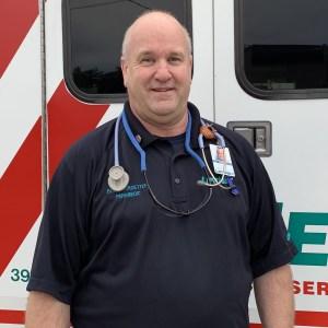 LIfeNet Paramedic Bob Flotkoetter, standing in front of a LIfeNet Ambulance.