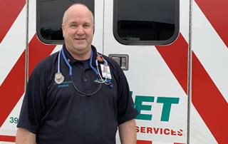 LIfeNet Paramedic Bob Flotkoetter standing in front of a LifeNet Ambulance.