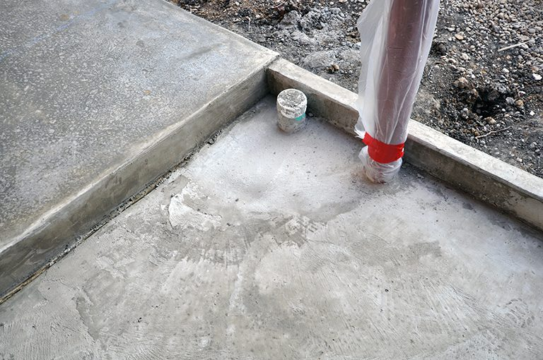 Drain set in slab under wood deck