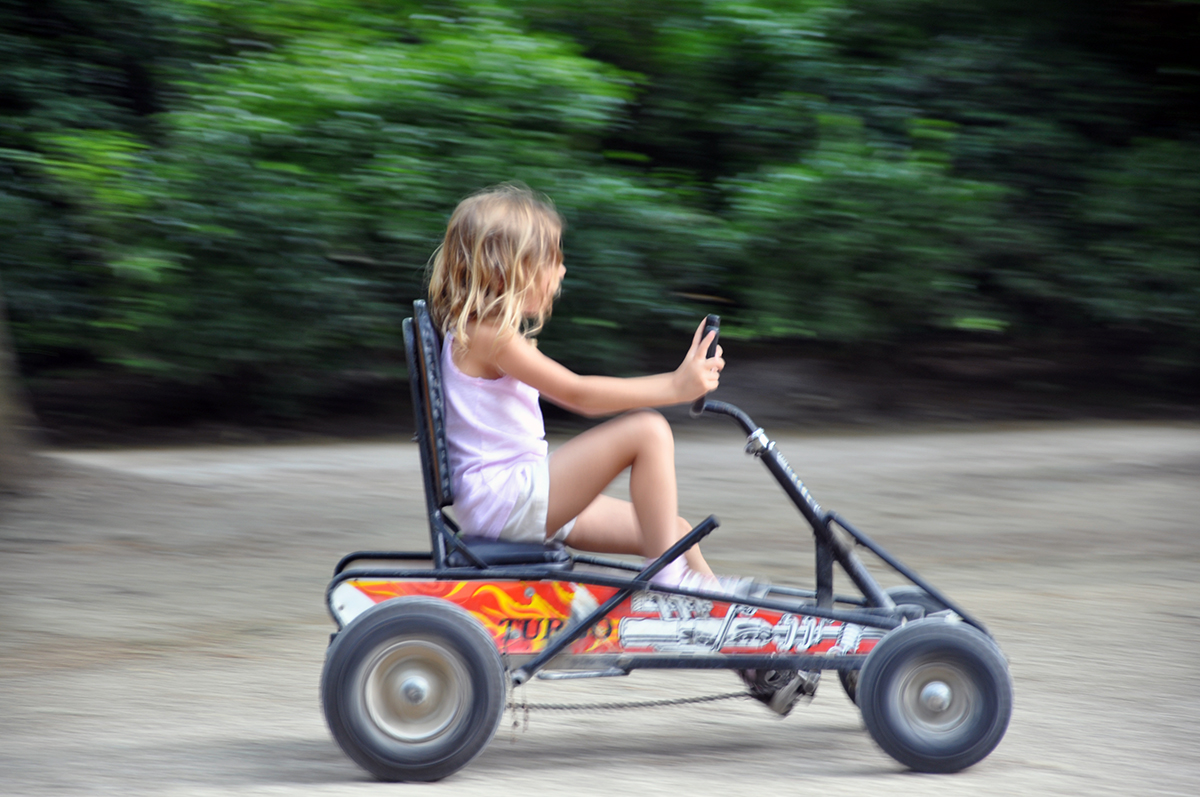 Kate Borson riding a go-cart in a park in Paris