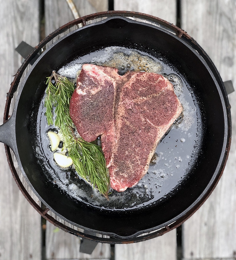 cooking a steak in a cast iron skillet - photo by Bob Borson