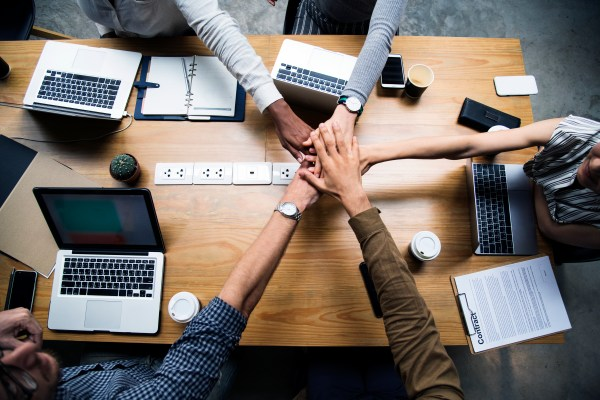Team of business people stacking hands Free Stock Photos