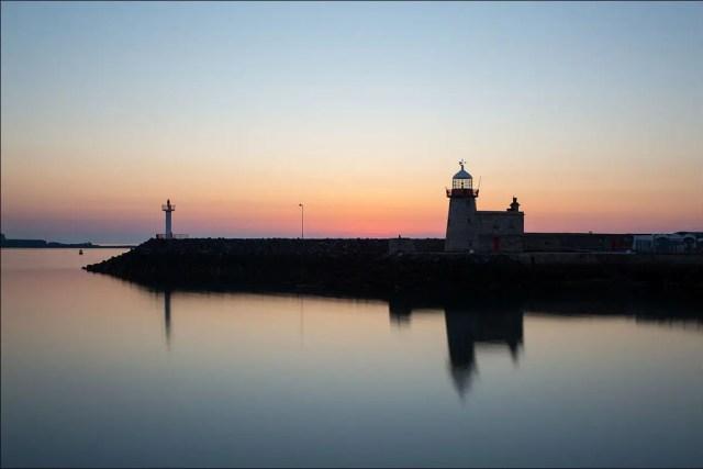 Sunrise over a harbor break wall.