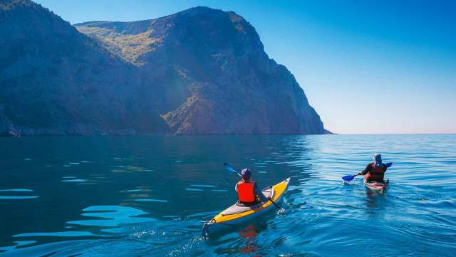 Two people kayaking with steep cliffs in the background.