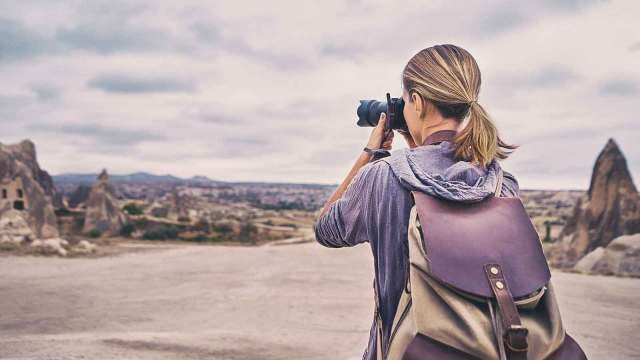 Woman taking photos of a hilly landscape.