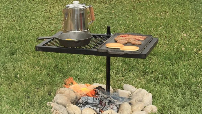 A texsport grill stake palced directly over a firepit with pancakes, bacon, sausage and eggs cooking, along with a camping coffee maker.