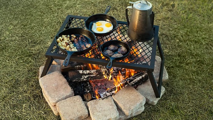 An Amazon Basics foldable grill table holding multiple skillets and a camp coffee maker.
