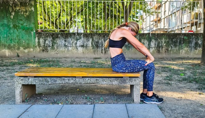 Woman doing an upper body stretch on a bench in the park.