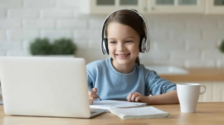 A young girl smiling at a joke her tutor made.