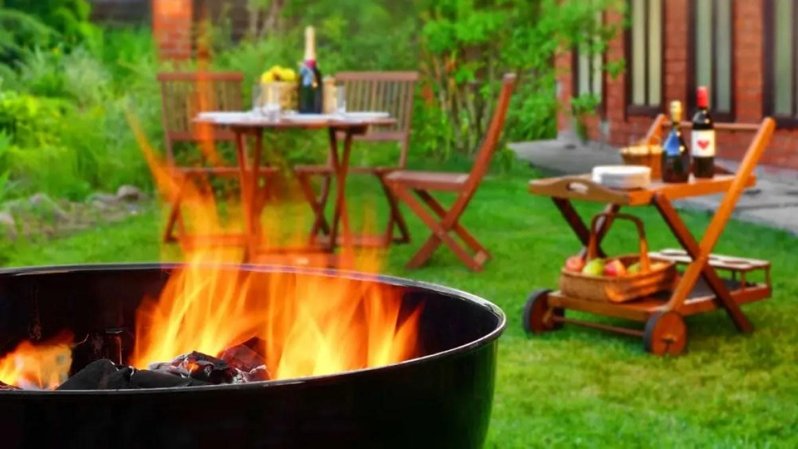 Двор с кострищем, садовой мебелью и тележкой для напитков.