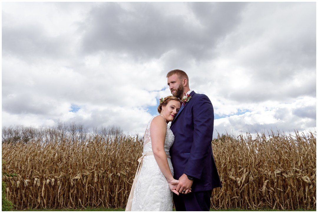 bride and groom poses with cornfield