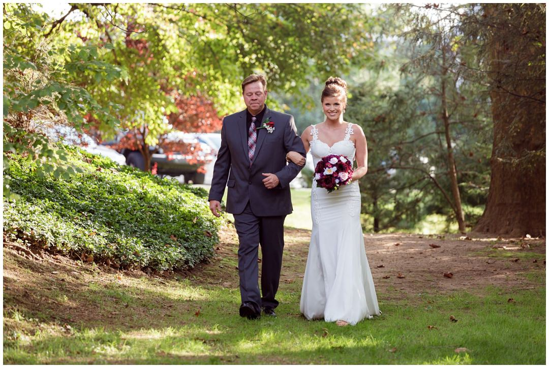 father walking daughter outdoor ceremony