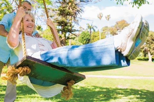 mature adults having fun on a swing outside