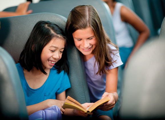 school bus safety - kids reading on bus