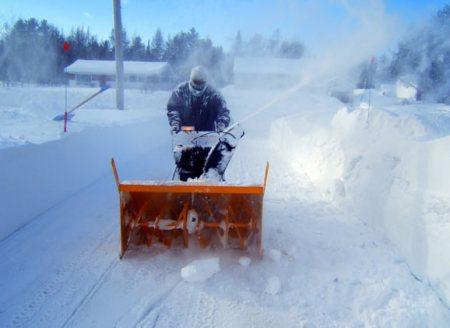 man snowblowing driveway in winter storm