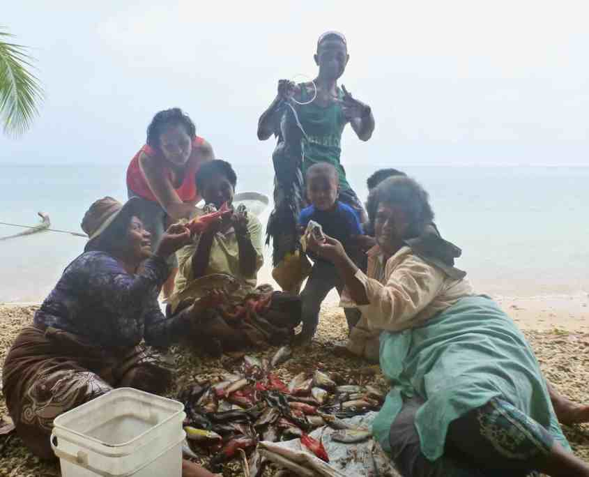 The Fijian women holding up the catch of the day