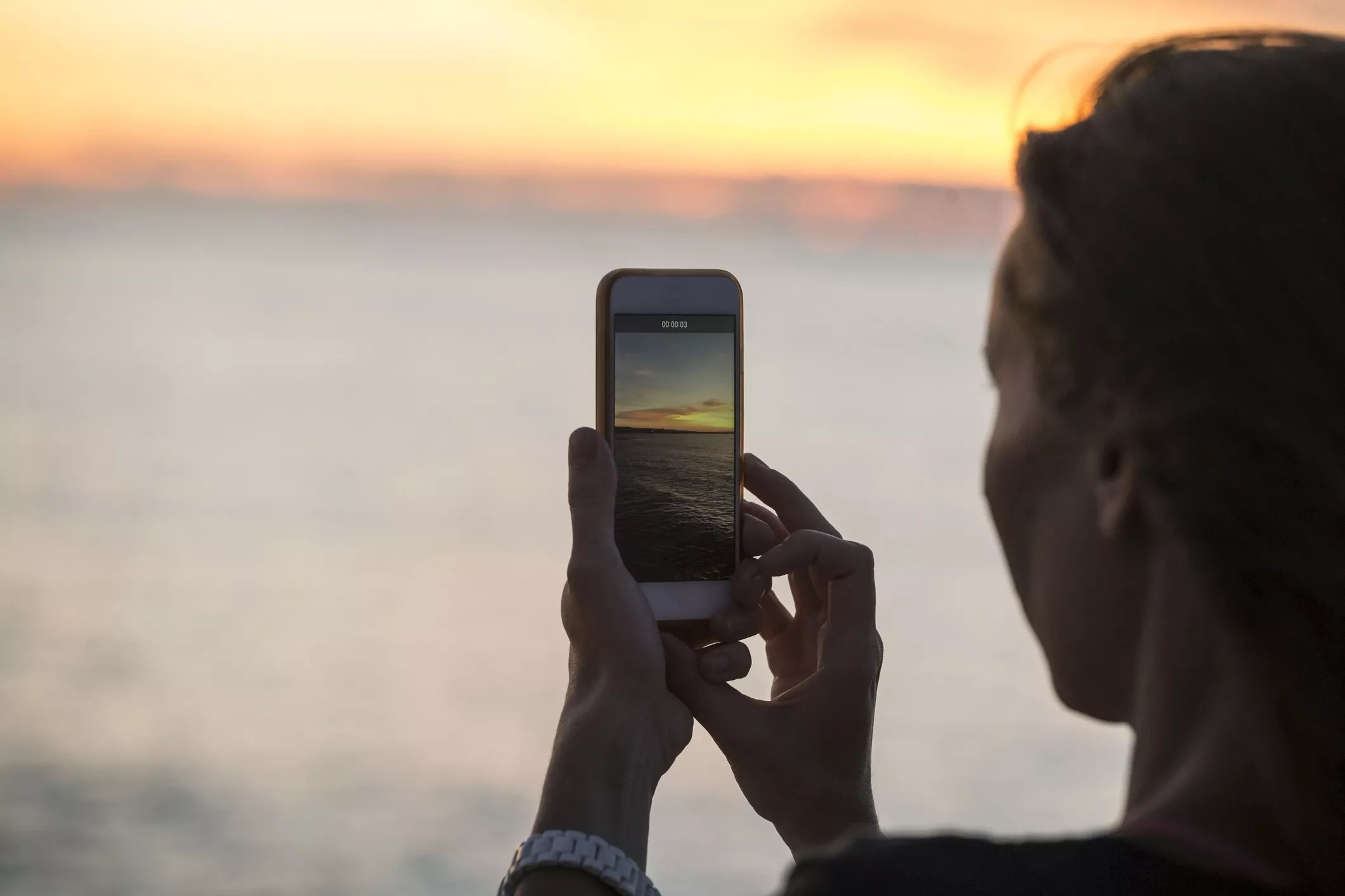 An image of a woman taking a photo of the sunset with her smartphone.